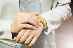 Guld- armbandarmringgarnering är hängeprydnaden med rosstil på kvinnahandleden under vitt ljus fotografering för bildbyråer