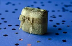 Guld- ask med garnering som en gåva på en blå bakgrund royaltyfri foto
