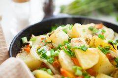 Guld- bakad potatis med grönsaker arkivfoto