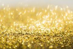 Guld- bakgrund, abstrakt guld- bokehljusberöm Royaltyfria Bilder
