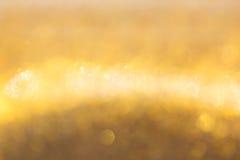 Guld- bakgrund, abstrakt guld- bokehljusberöm Arkivbilder