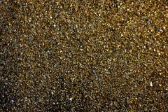 Guld- bakgrund - damm av guld över svart bakgrund Royaltyfri Bild
