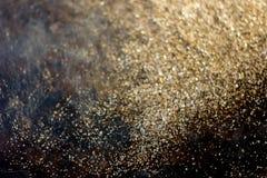 Guld- bakgrund - damm av guld över svart bakgrund Arkivfoton