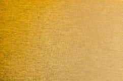 Guld- bakgrund för färgtygtextur Royaltyfria Bilder