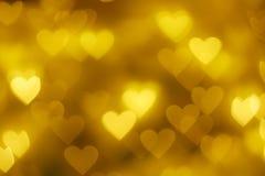 Guld- bakgrund för hjärtaformbokeh Royaltyfri Bild