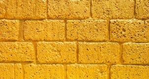 Guld- bakgrund för textur för abstrakt begrepp för tegelstenvägg royaltyfri foto