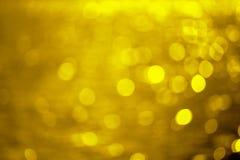 Guld- bakgrund som skapas från bild av guld- bokehvatten arkivfoto