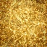 Guld- bakgrund texturerar Arkivbild