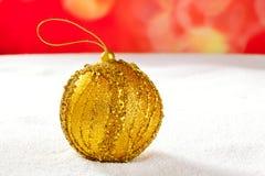 Guld- bauble för jul på snow och red Fotografering för Bildbyråer