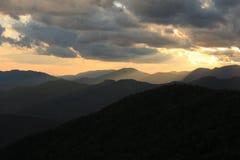 Guld- bergig solnedgång royaltyfria bilder