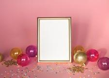 Guld- bildram med julprydnader Modell på rosa bakgrund med konfettier Modegarnering Royaltyfri Bild