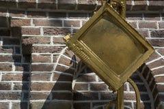 Guld- bildskärm som skulptur med tegelstenväggen som bakgrund Arkivbilder