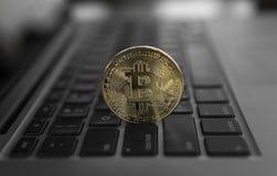 Guld- Bitcoin crypto mynt på ett bärbar datortangentbord Utbyte affär, reklamfilm Vinst från att bryta kryptavalutor royaltyfria bilder