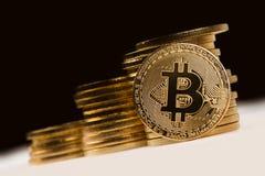 Guld- bitcoin framme av en hög av guld- metalliska mynt på bl Royaltyfria Foton