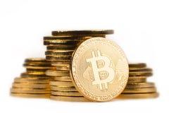 Guld- bitcoin framme av en hög av guld- metalliska mynt på wh Arkivbild