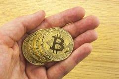 Guld- bitcoin i en hand för man` s Symbol av en ny faktisk valuta illustration 3d Arkivfoto