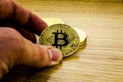 Guld- bitcoin i en hand för man` s Symbol av en ny faktisk valuta illustration 3d Arkivbild