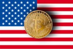 Guld- bitcoin med den suddiga flaggan av Förenta staterna i bacen arkivbild