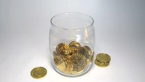 Guld- Bitcoin mynt faller in i en spargris Begrepp för Digital crypto valutabesparingar lager videofilmer