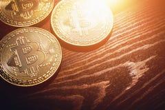 Guld- Bitcoin mynt - nya faktiska pengar på träbakgrund med ljus effekt Arkivfoton