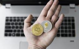 Guld- bitcoin och Ethereum mynt i hand för man` s med en bärbar dator på bakgrund Man som rymmer en crypto valuta i hand Arkivbild