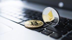 Guld- bitcoin och Ethereum mynt på en bärbar dator Crypto valuta på ett datorsvarttangentbord Digital valuta faktiskt Royaltyfri Bild