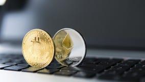 Guld- bitcoin och Ethereum mynt på en bärbar dator Crypto valuta på ett datorsvarttangentbord Digital valuta faktiskt Royaltyfria Bilder