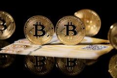Guld- Bitcoin och sedlar arkivfoto