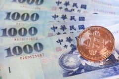 Guld- bitcoin på bakgrund 1000 för Taiwanease dollarräkningar, med Arkivbild