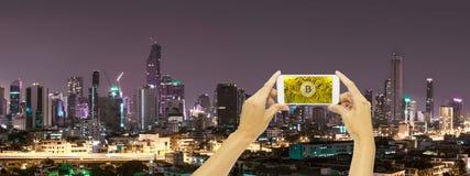 Guld- bitcoin på den smarta telefonen för skärm med byggnad i Bangkok royaltyfri fotografi