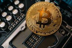 Guld- Bitcoin på det utskrivavna datormoderkortet Arkivfoton