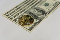Guld- bitcoin på hundra dollarräkningar arkivbild