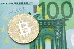 Guld- bitcoin på sedel för euro 100 Arkivbild