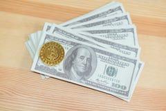Guld- Bitcoin som förläggas på sedlar för en 100 dollar Digital valutabegrepp kan vara van vid gör online-köp Royaltyfri Bild