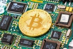 Guld- bitcoin som ligger över del för elektronisk dator Royaltyfria Foton