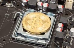 Guld- bitcoin som ligger över del för elektronisk dator Affär Arkivbild