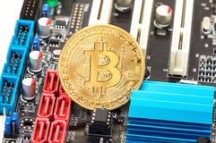 Guld- bitcoin som ligger över del för elektronisk dator Affär Royaltyfri Fotografi