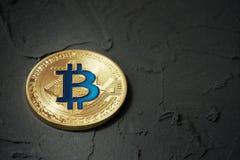 Guld- bitcoin som ligger på ett mörker, rappad yttersida arkivfoton