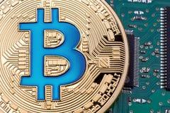 Guld- Bitcoin valuta på en bakgrund för strömkretsbräde Arkivfoton