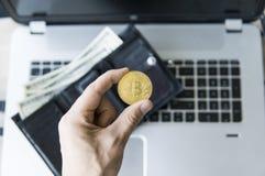 Guld- bitcoinmynt i hand för man` s med en bärbar dator på bakgrunds- och läderplånboken med pengar Man som rymmer ett crypto Fotografering för Bildbyråer