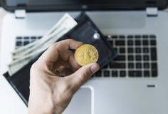 Guld- bitcoinmynt i hand för man` s med en bärbar dator på bakgrunds- och läderplånboken med pengar Man som rymmer ett crypto Arkivbilder