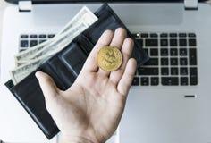 Guld- bitcoinmynt i hand för man` s med en bärbar dator på bakgrunds- och läderplånboken med pengar Man som rymmer ett crypto Arkivfoto