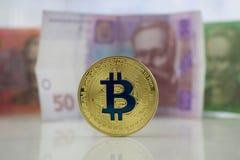 Guld- bitcoinmynt och Ukraina pengar Royaltyfria Foton