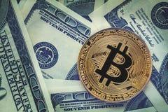 Guld- bitcoinmynt på bakgrund för dollarräkningar Cryptocurrency och kontant pengarbankrörelsebegrepp royaltyfria bilder