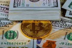 Guld- bitcoinmynt på hundra bakgrund för US dollarräkningar Cryptocurrency ny digital valuta, Bitcoin utbyte till dollaren måndag arkivfoto