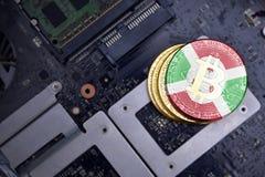 Guld- bitcoins med flaggan av Burundi på ett bräde för elektronisk strömkrets för dator Bitcoin som bryter begrepp royaltyfri bild