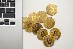 Guld- bitcoins som visas från ovanför sidan av silverbärbara datorn arkivbild