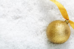 Guld blänker baublen på snow Arkivbild