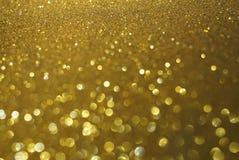 Guld blänker bokehabstrakt begreppbakgrund arkivbild