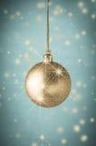 Guld blänker julstruntsaken på turkos med stjärnor Royaltyfri Foto
